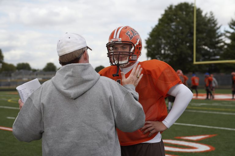 Coach speaking with football player