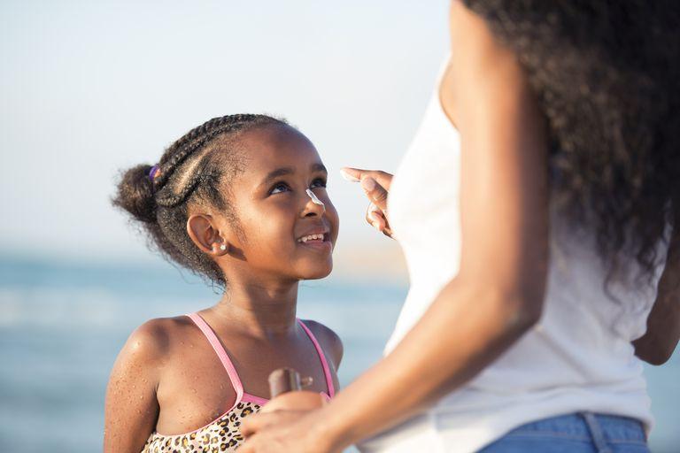 Mom applying sunscreen to daughter