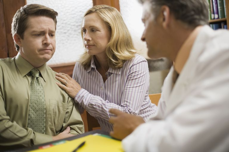 ibs and fissures. Worried couple in office with doctor