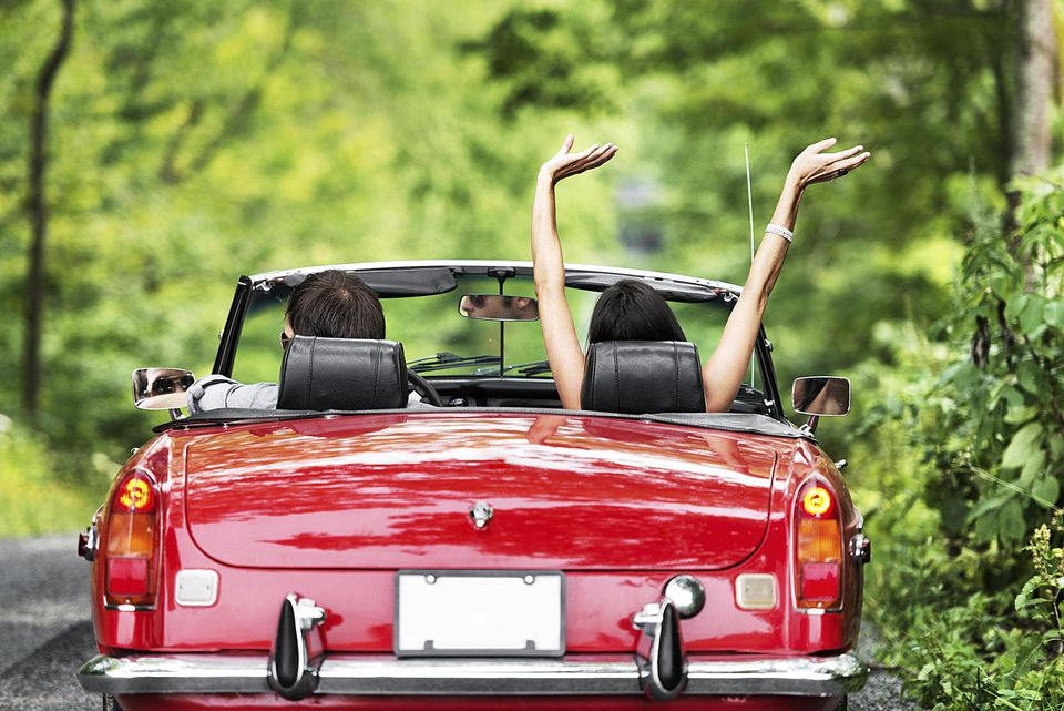 couple in convertible driving a highway yard sale in summer