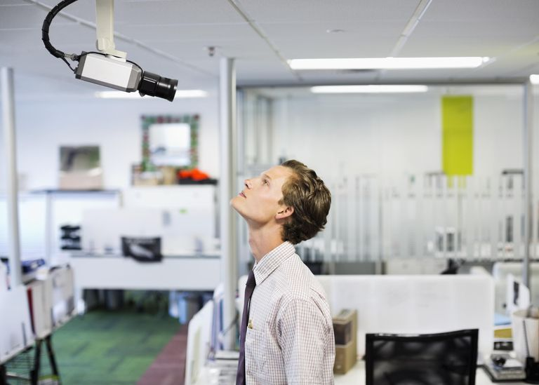 Businessman examining security camera in office