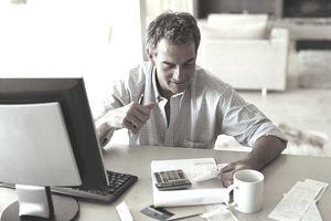 Mature man sitting at desk checking receipts