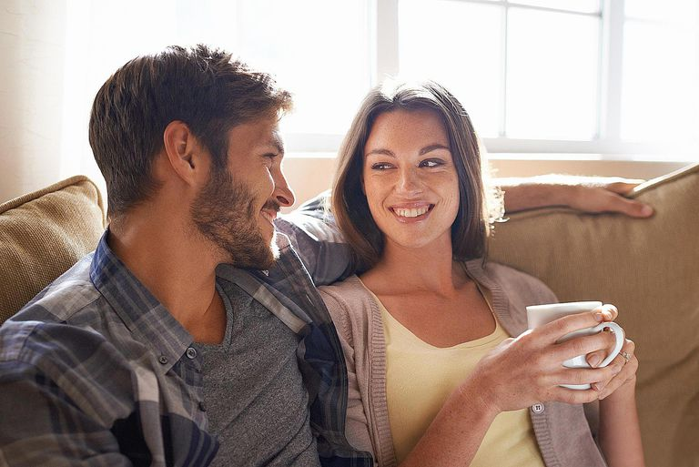 Couple sitting on couch drinking coffee