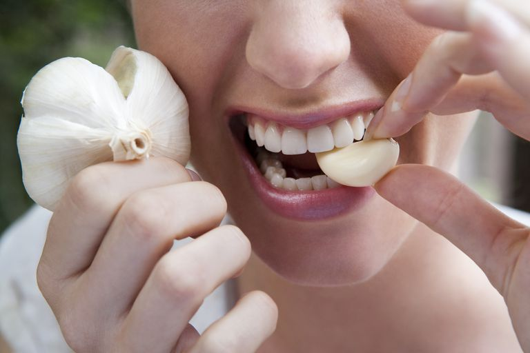Woman biting into clove of garlic