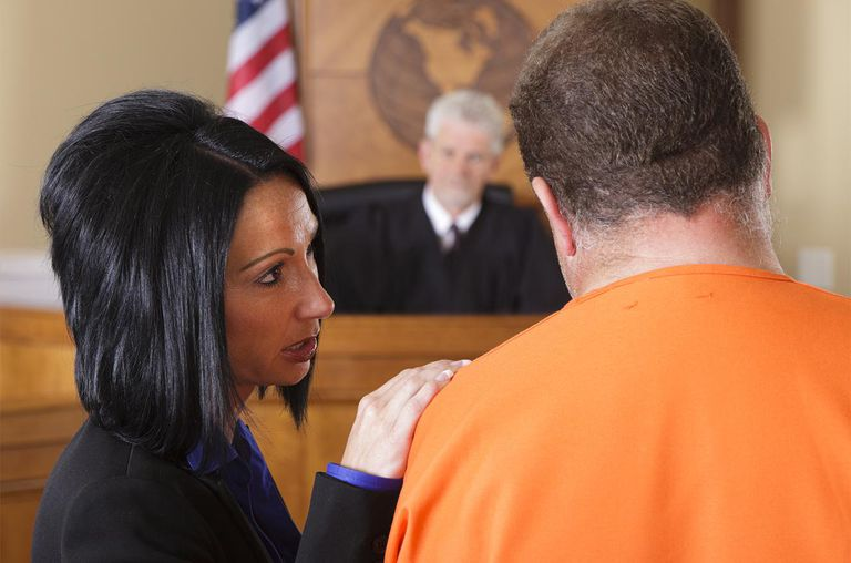 A lawyer advising her client before the judge in a criminal trial.