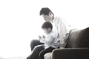 Father and son watching a smart phone together