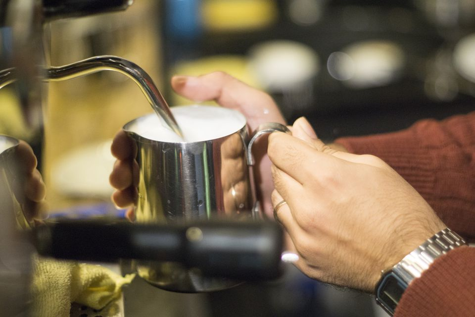 Barista using coffee machine to steam milk in metal jug