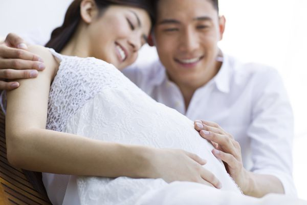 Pregnant woman with partner's hand on her belly, pregnant with PCOS