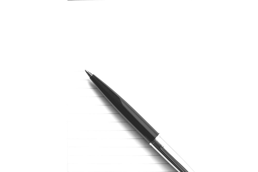 Ballpoint pen sat on blank lined writing pad