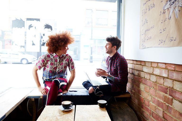 Two friends chatting in coffee shop window.