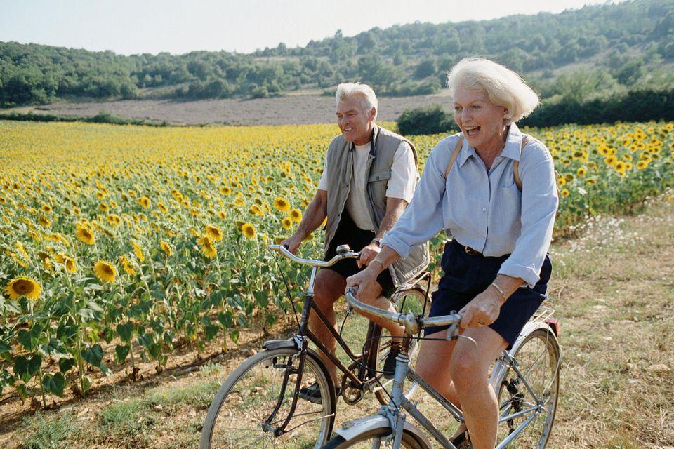 Senior couple riding bikes through a field of sunflowers
