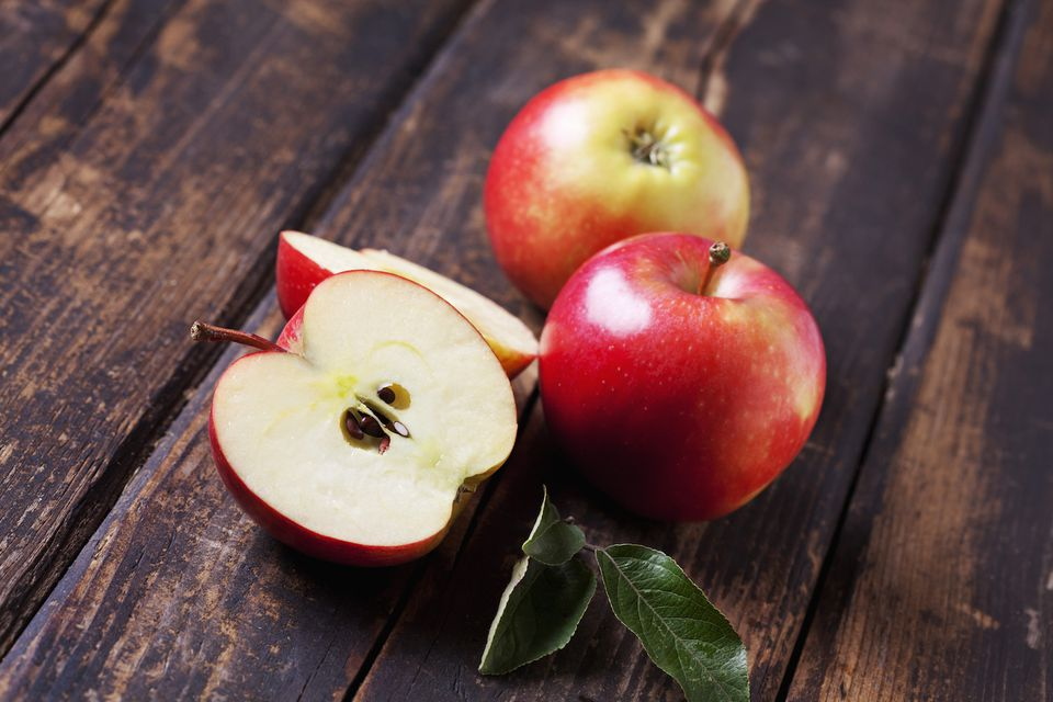 Whole and sliced red apples on dark wood