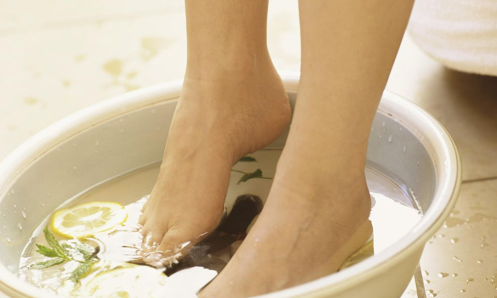 Person soaking feet in lemon and mint