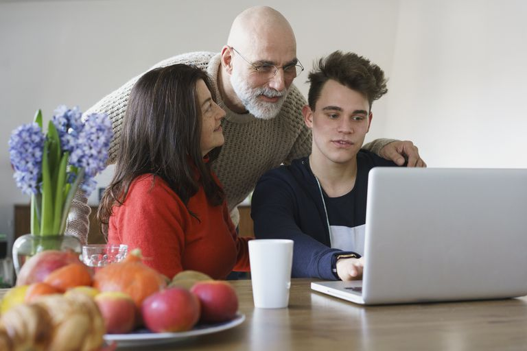 Family discussing while looking at laptop on table at home