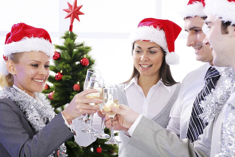 Four people drink wine together during the holidays