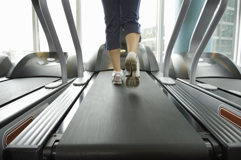 Woman excursing on treadmill, low section