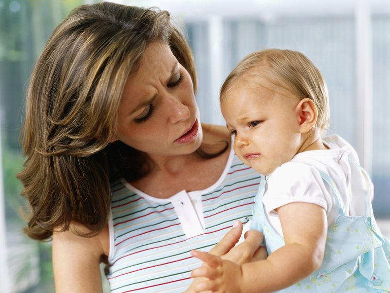 Woman holding baby worried