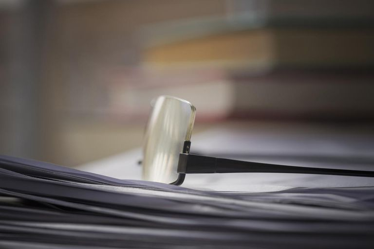 Close up of glasses on stack of papers