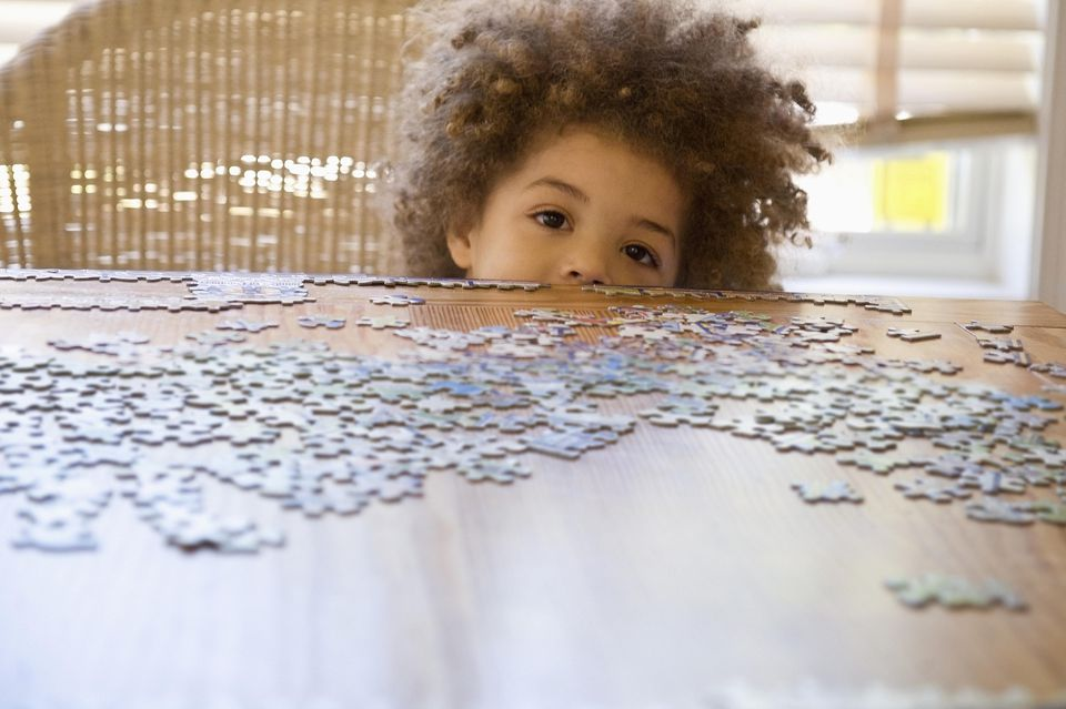 Little boy completing jigsaw puzzle
