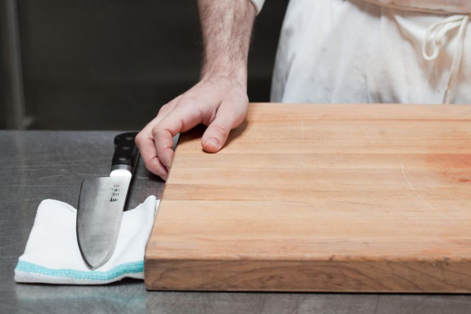 Close up of butcher with chopping board and knife