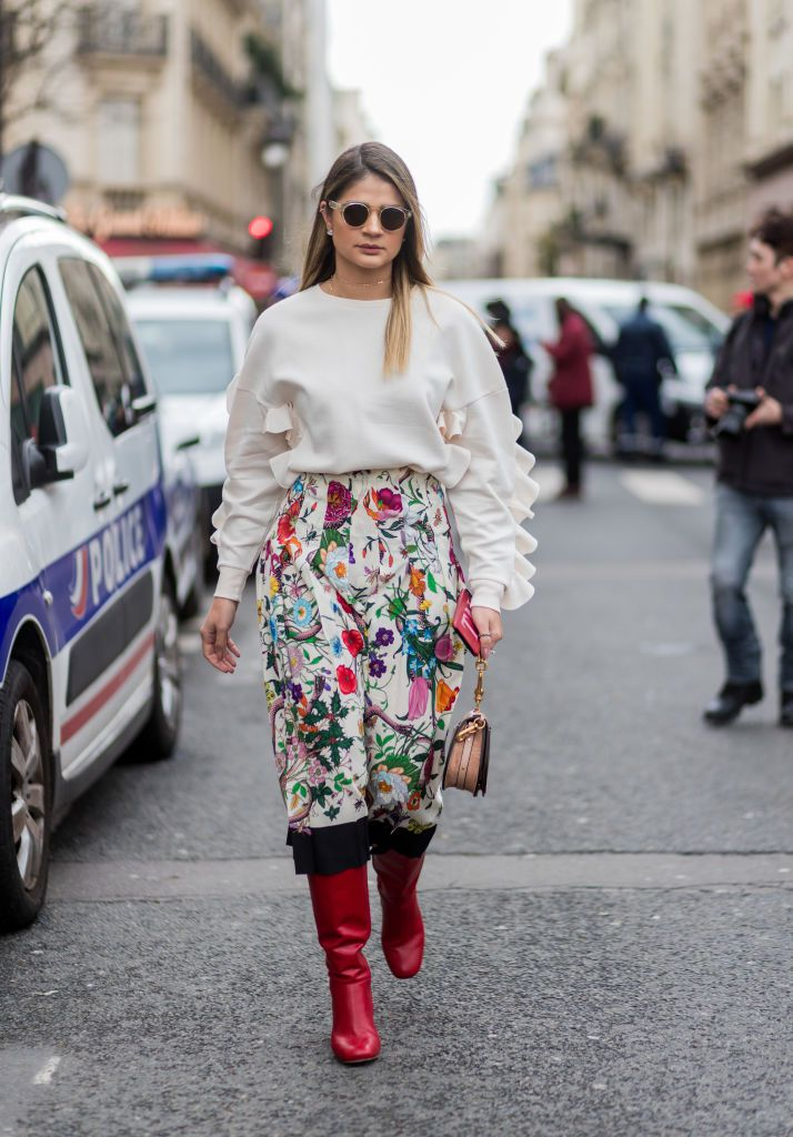 Street style in sweater and floral print skirt and boots