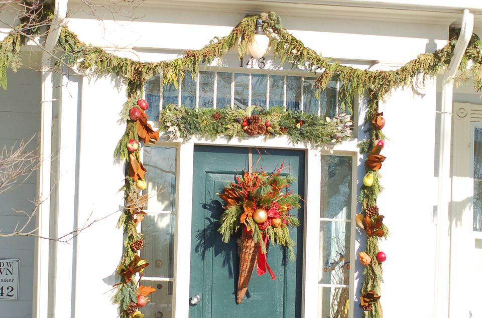 Evergreen garland hung over a door (ornamented with a cornucopia) as a Christmas decoration.