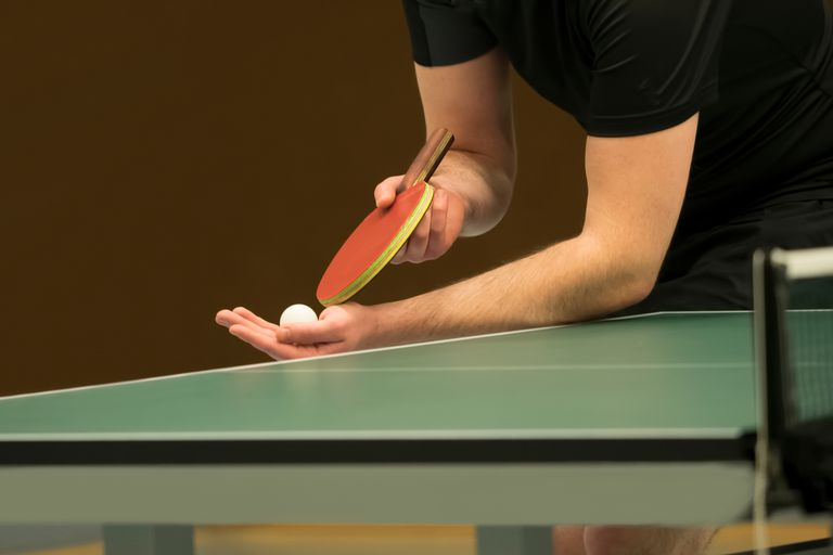 Midsection Of Man Serving While Playing Table Tennis