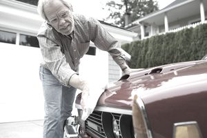 Senior man waxing classic car in driveway