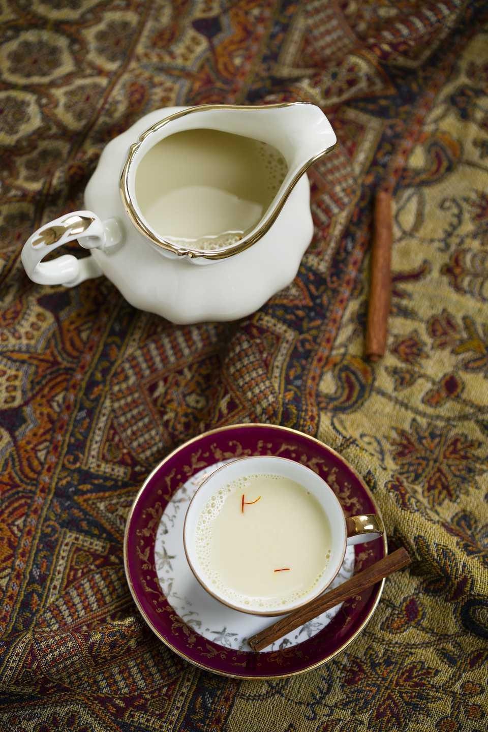 Milk pitcher and demitasse cup of milk spiced with saffron and cinnamon on cloth