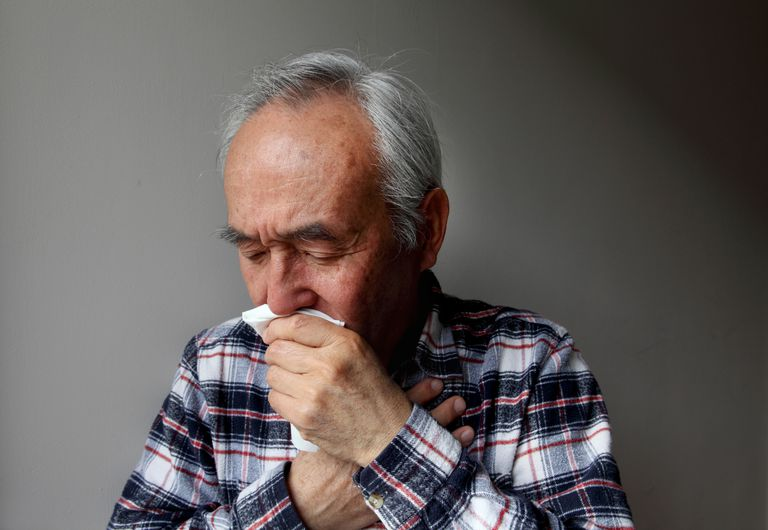 man coughing into napkin