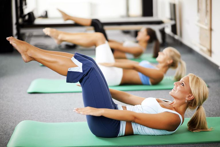 Three women sitting on the exercising mat and doing abdominal exercises.