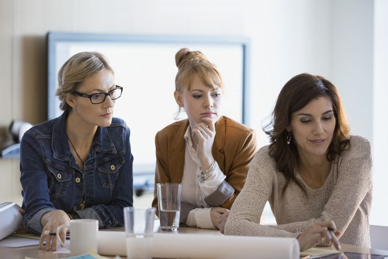 Focused businesswoman with blueprints in meeting