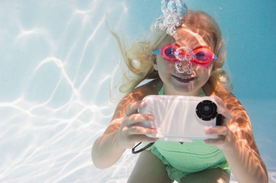 Caucasian girl taking photograph underwater in pool