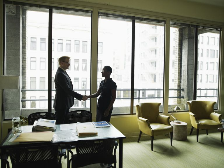 Two businesspeople shaking hands in office