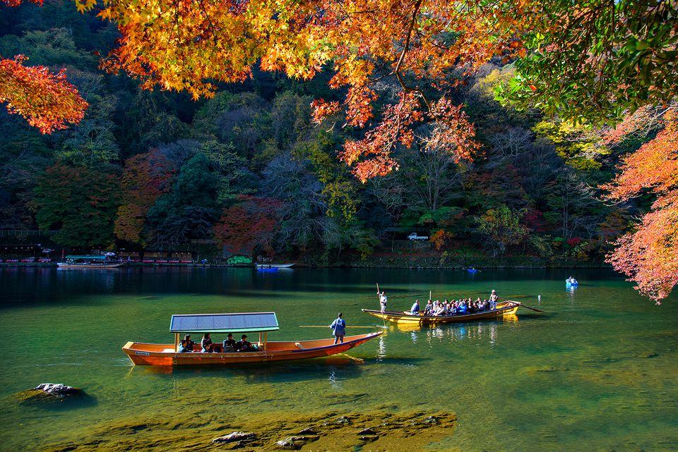 Tourist boats run along Hozugawa River in Autumn Morning