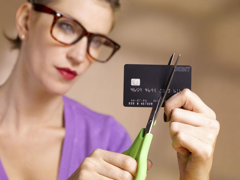 Woman cutting up credit card.