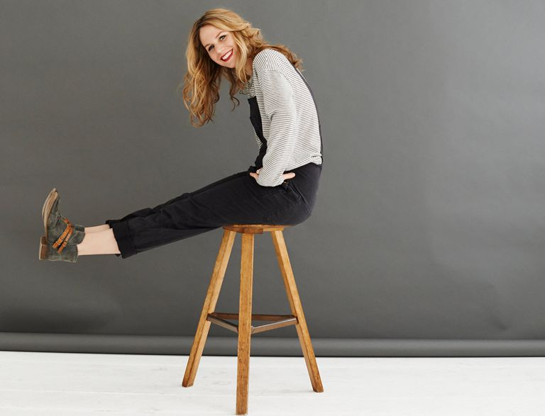 Woman sitting on a three-legged stool