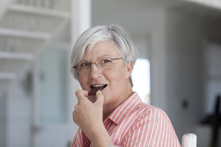 senior woman eating chocolate