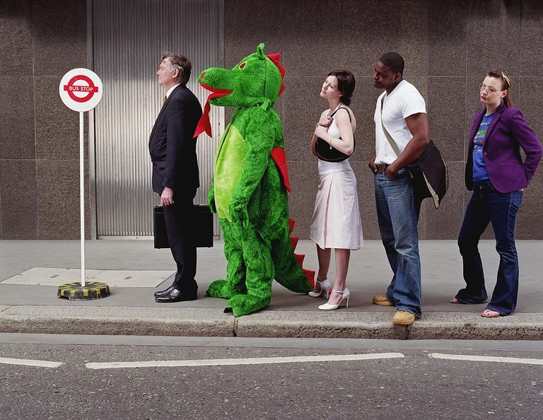 A person dressed in a dragon costume standing in bus stop line.