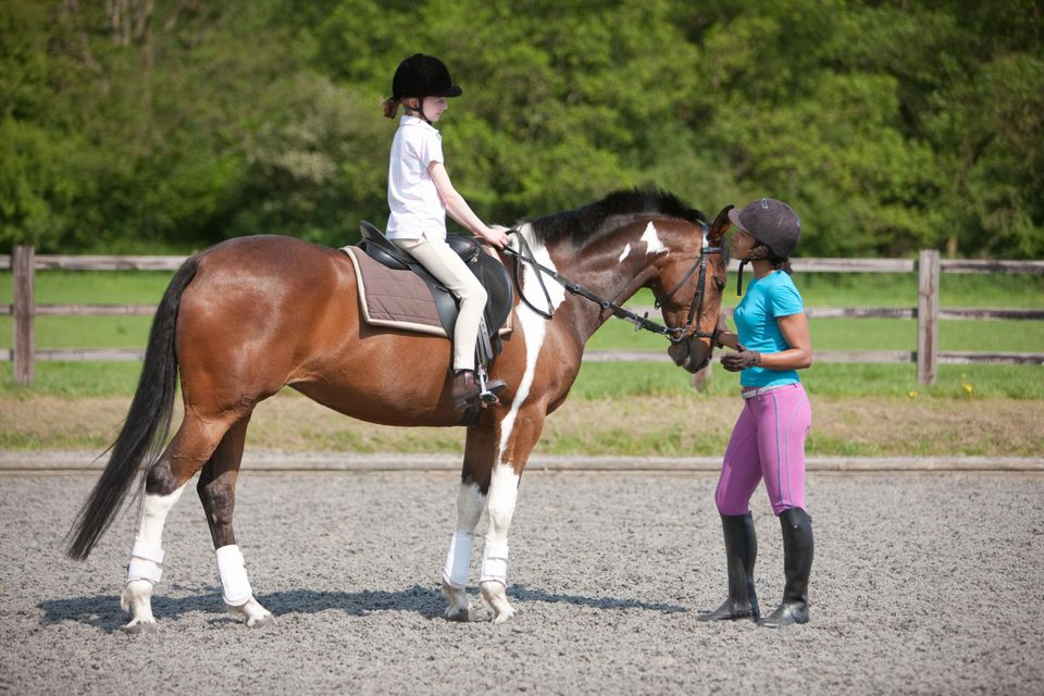 Young girl on horseback with riding instructor.