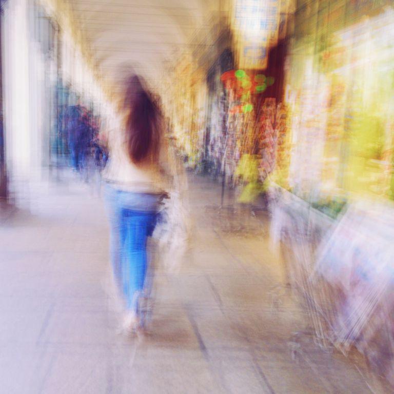 Blurred Motion Of Woman Walking On Street