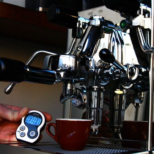 An image of a barista timing an espresso shot with a digital stopwatch.