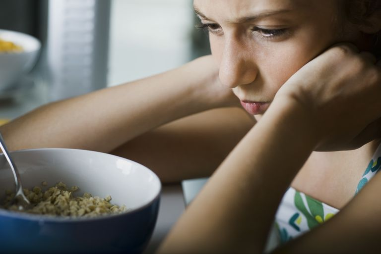 Girl sulking at table, glaring at bowl of cereal