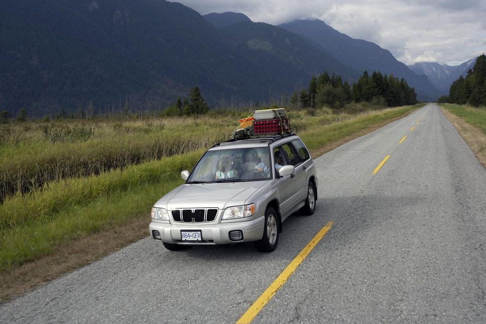 Couple driving sports utility vehicle along rural road