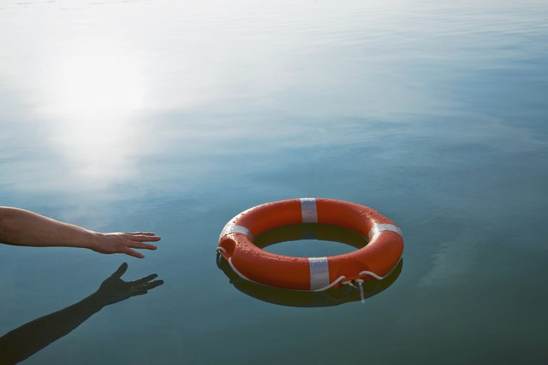 Arm reaching for a life preserver - symbolic of a 401(k) hardship withdrawal.