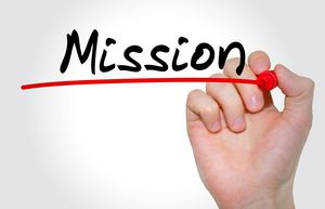 Hand writing the word mission on a white board.