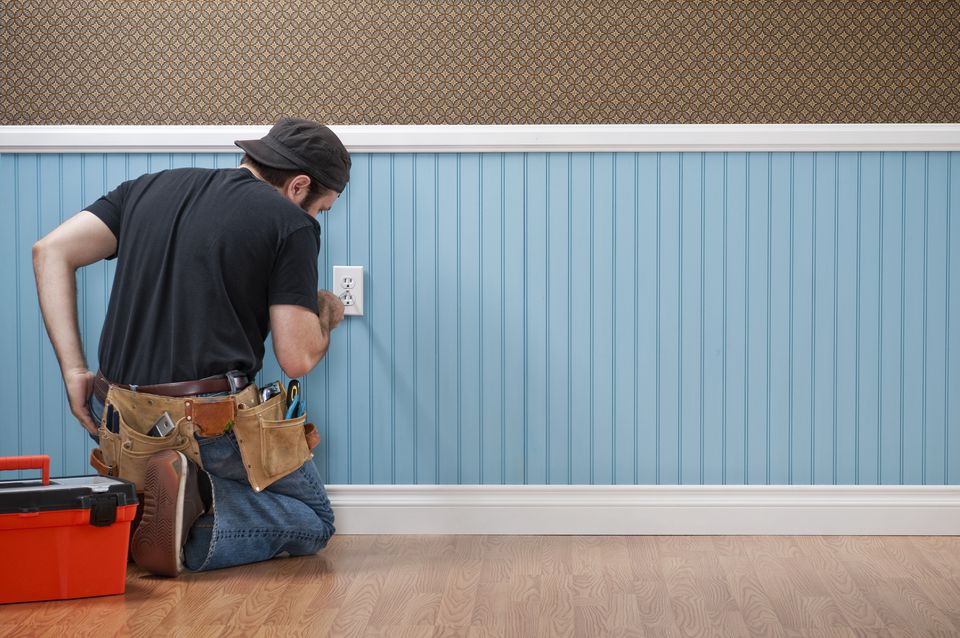 A handyman working on an electrical outlet