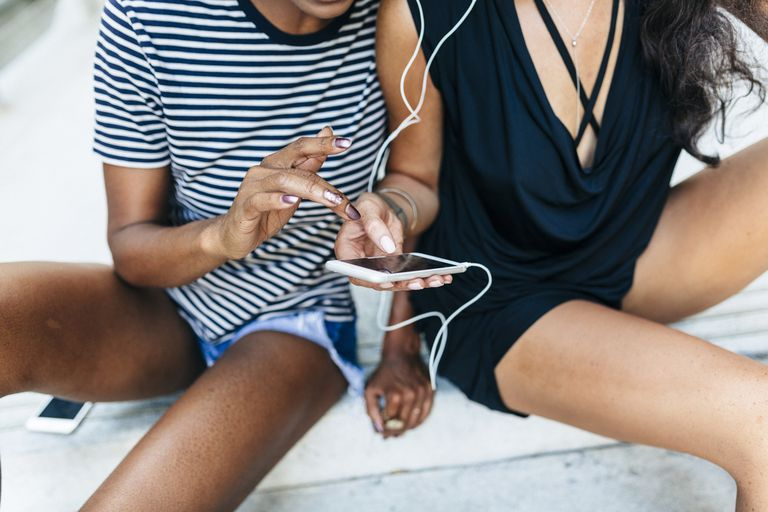 Two friends sitting on stairs listening music together with earphones and smartphone, partial view