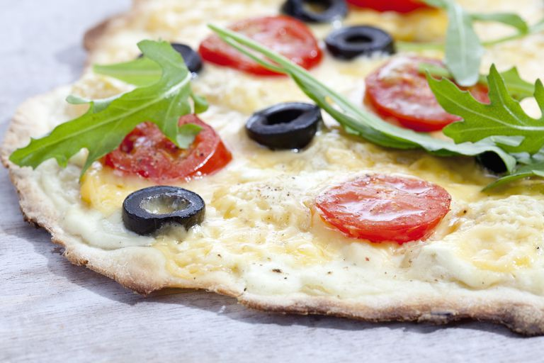 Tarte with black olives, tomatoes and rocket salad, close up