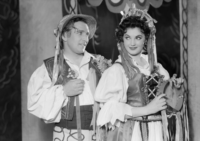 A couple exchange loving looks in a scene from Smetana's 'The Bartered Bride' presented by the Sadler's Wells Opera Company at Sadler's Wells, London. Cast included Peter Glossop, Victoria Elliott, and David Ward. April 3, 1956.